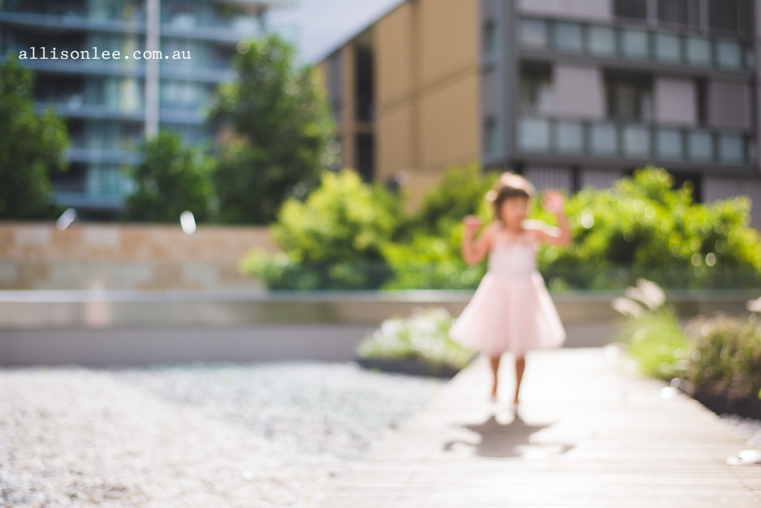 Five year old in pink ballet dress playing in rock garden in Pyrmont