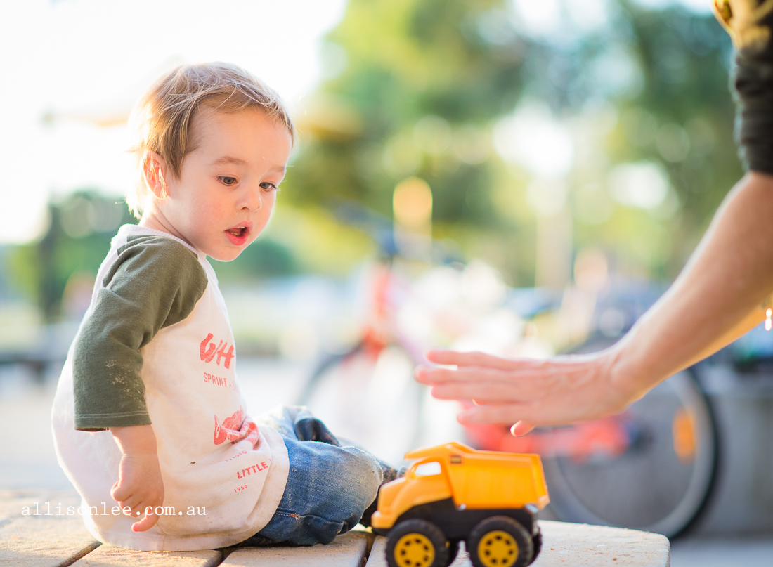 Child playing with trucks at park on harbour