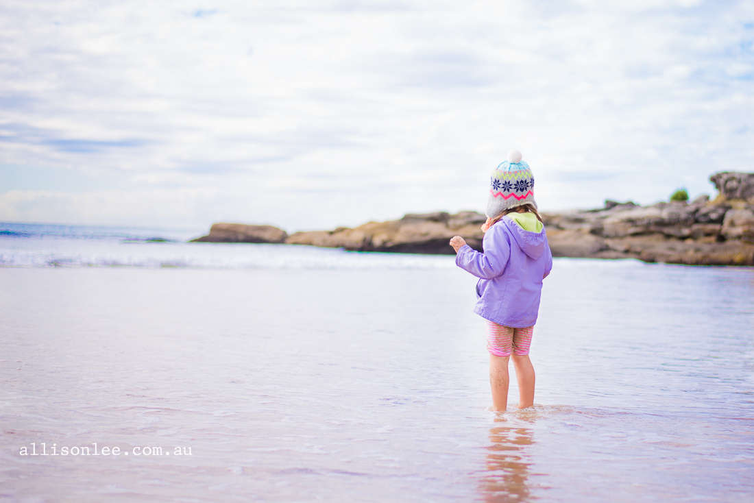 Four year old girl at Manly beach in winter