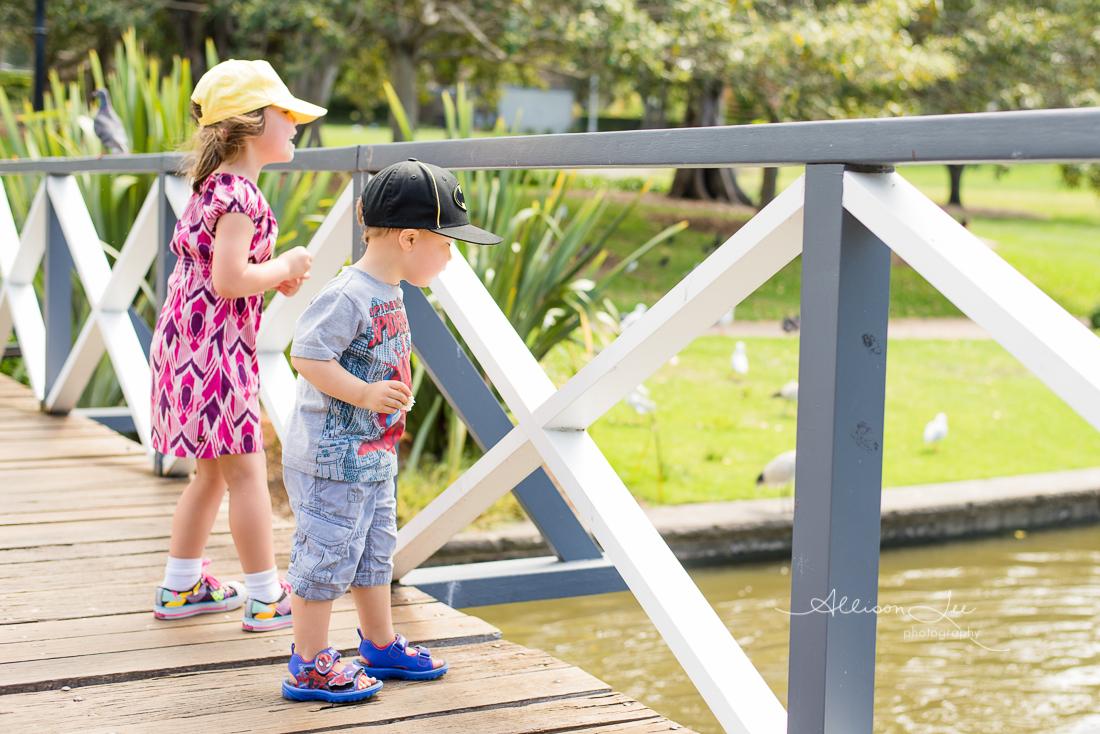 Siblings feeding ducks in Victoria Park