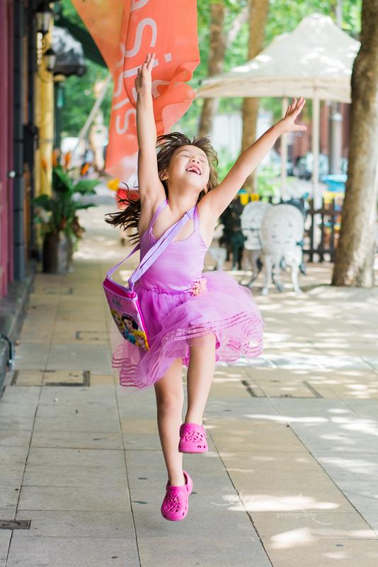 Portrait of girl jumping for joy in purple dress
